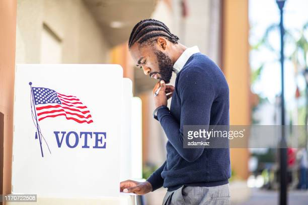millenial black man voting in election - election voting stock pictures, royalty-free photos & images