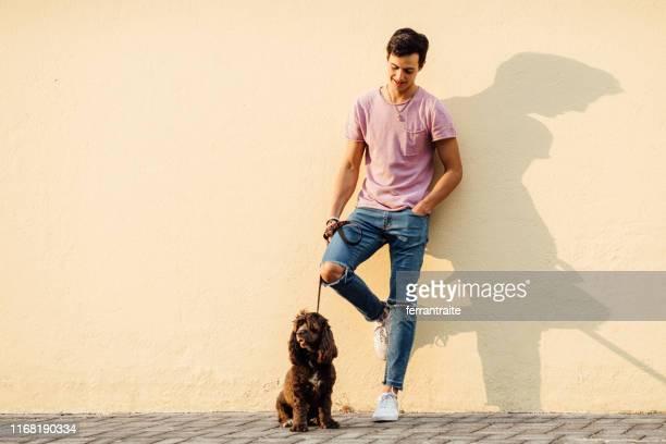 彼の犬を歩くミレニアル世代の少年 - street style ストックフォトと画像