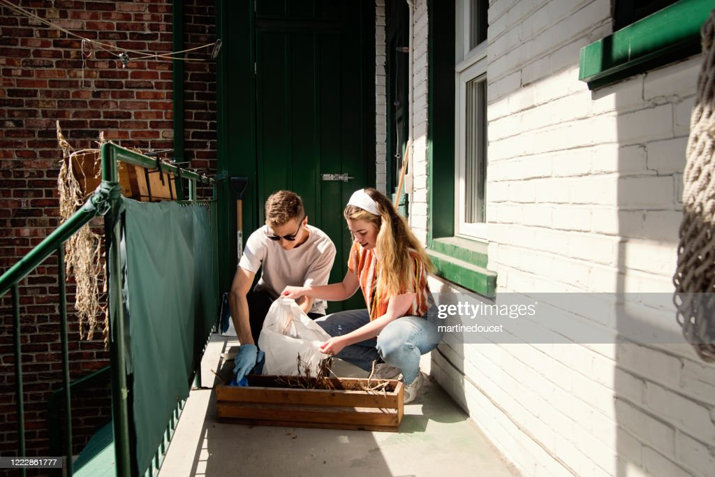 Millenial couple cleaning city balcony in spring. : Stock Photo