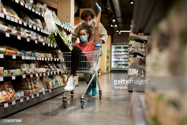 a millenial couple riding a cart in a grocery sotre. - wide shot stock pictures, royalty-free photos & images