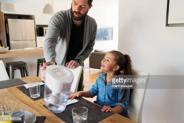 """padre milenario con hija pequeña almorzando en casa. - """"martine doucet"""" or martinedoucet fotografías e imágenes de stock"""