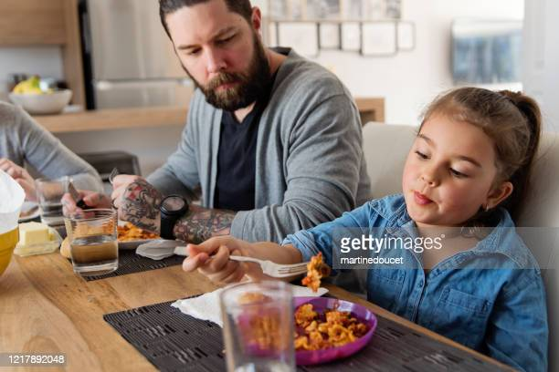 """millenial father with young daughter eating lunch at home. - """"martine doucet"""" or martinedoucet stock pictures, royalty-free photos & images"""