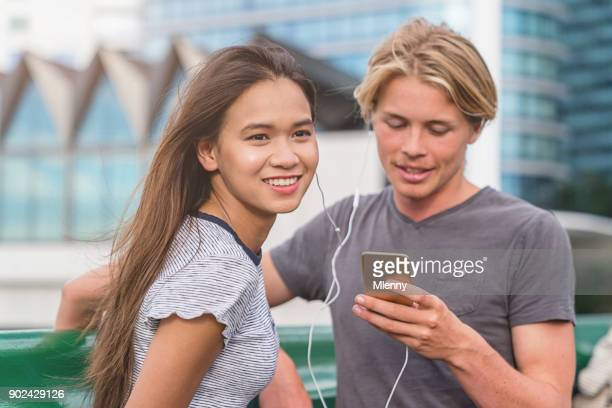 Millenial generation couple listening to music Pyrmont Bridge Darling Harbour Sydney