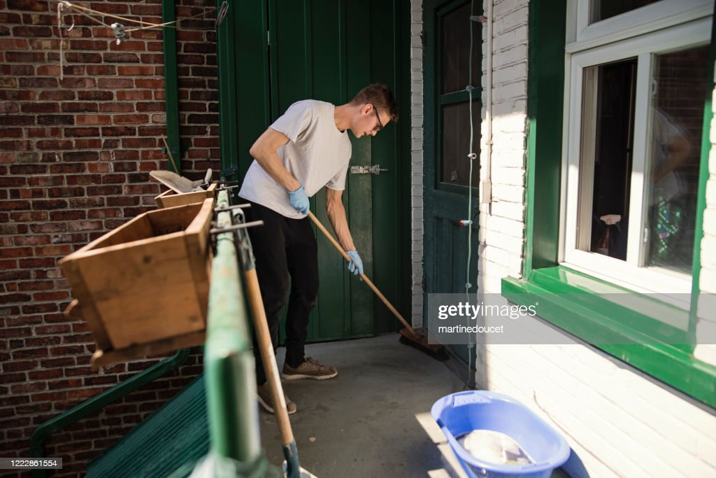 Millenial man cleaning city balcony in spring. : Stock Photo