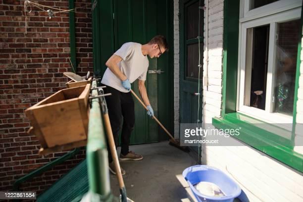 """homem millenial limpando a varanda da cidade na primavera. - """"martine doucet"""" or martinedoucet - fotografias e filmes do acervo"""
