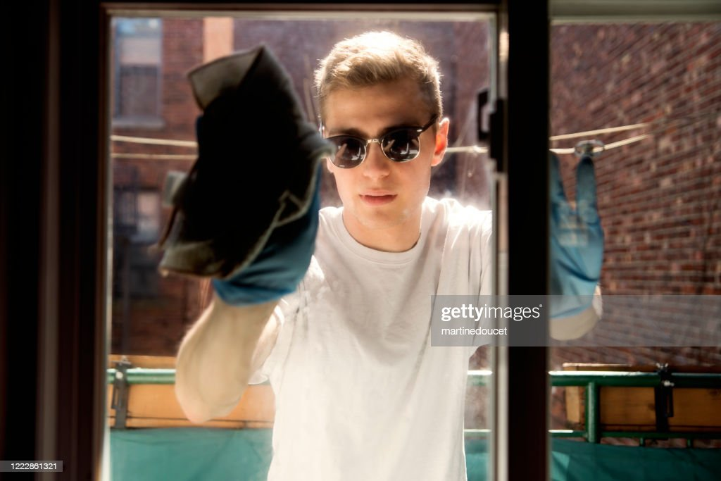 Millenial man cleaning window on city balcony in spring. : Stock Photo