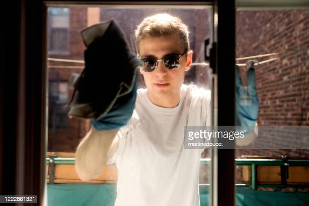 """millenial man cleaning window on city balcony in spring. - """"martine doucet"""" or martinedoucet stock pictures, royalty-free photos & images"""