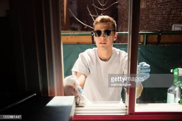 """millenial man limpando janela na varanda da cidade na primavera. - """"martine doucet"""" or martinedoucet - fotografias e filmes do acervo"""