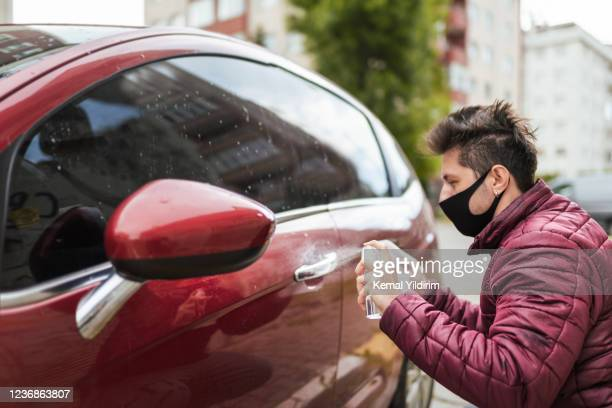 millenial man in face mask cleaning his car with wet wipe and antiseptic - antiseptic wipe stock pictures, royalty-free photos & images