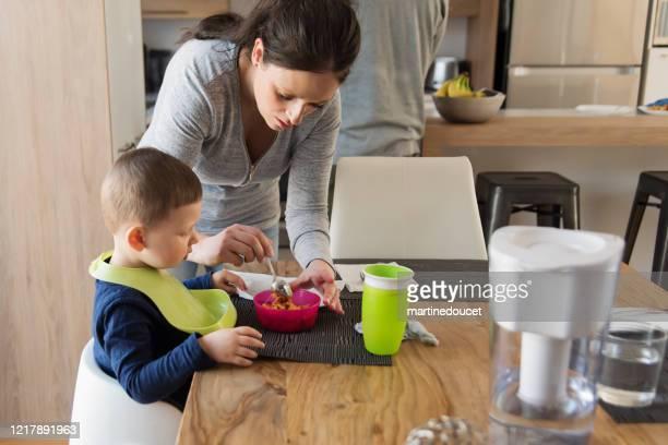 """madre millenial ayudando a su hijo pequeño a almorzar en casa. - """"martine doucet"""" or martinedoucet fotografías e imágenes de stock"""