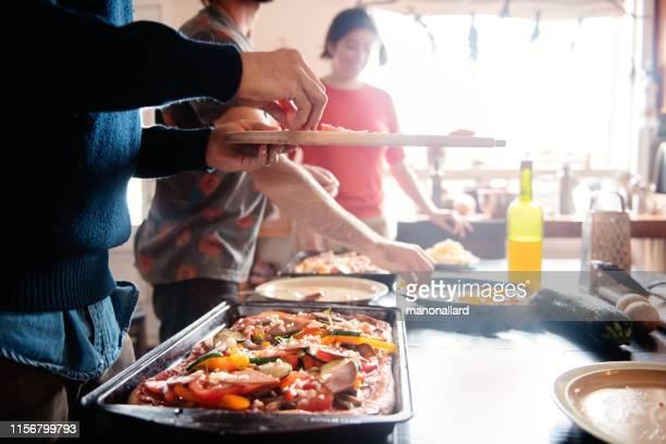 millenial coinquilini multietnici cucinano vegetalian, pizza vegana - preparation foto e immagini stock
