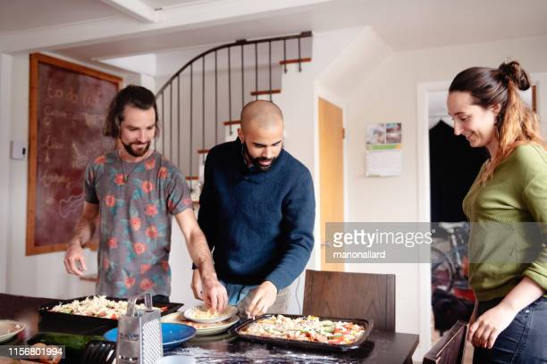 millenial multi-ethnic roommates cooking vegetalian, vegan pizza - creole ethnicity stock pictures, royalty-free photos & images