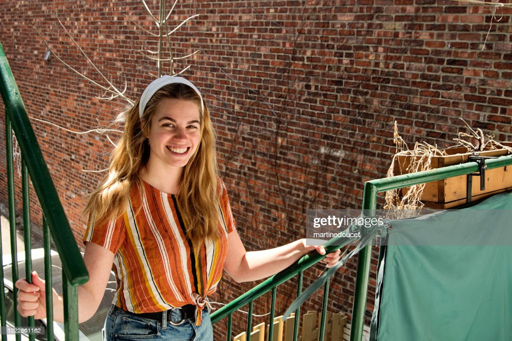 Millenial woman cleaning city balcony in spring. : Stock Photo