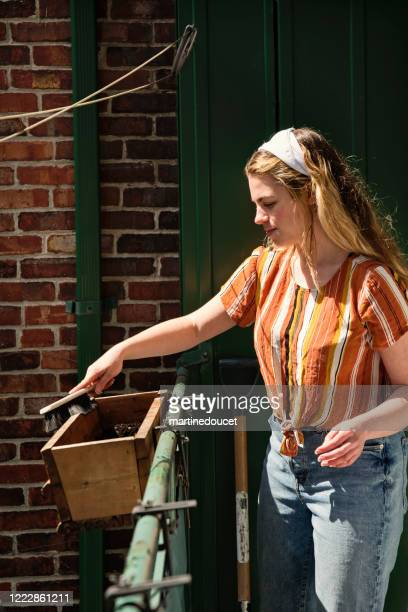 "millenial woman cleaning city balcony in spring. - ""martine doucet"" or martinedoucet stock pictures, royalty-free photos & images"