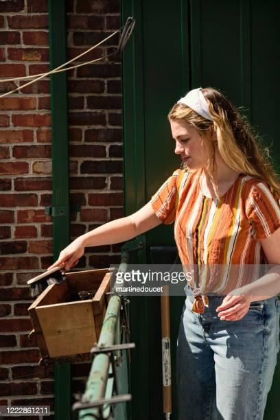 """mulher millenial limpando a varanda da cidade na primavera. - """"martine doucet"""" or martinedoucet - fotografias e filmes do acervo"""
