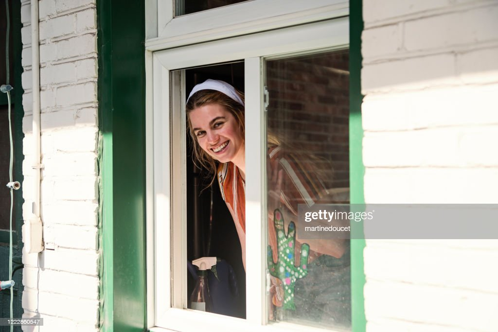 Millenial woman cleaning window on city balcony in spring. : Stock Photo