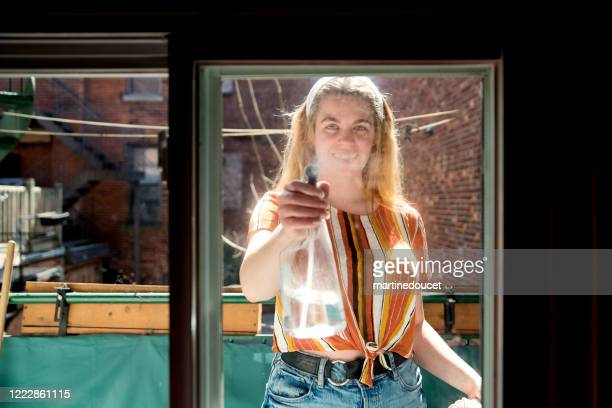 "millenial woman cleaning window on city balcony in spring. - ""martine doucet"" or martinedoucet stock pictures, royalty-free photos & images"