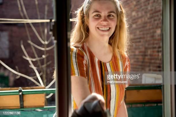 """millenial mulher limpando janela na varanda da cidade na primavera. - """"martine doucet"""" or martinedoucet - fotografias e filmes do acervo"""