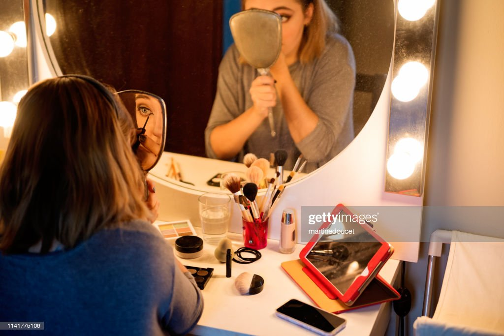 Millenial woman doing make-up following a tutorial. : Stock Photo