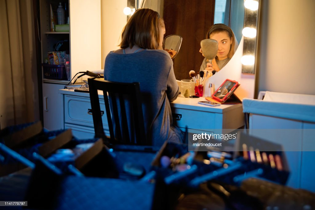 Millenial woman doing make-up following a tutorial. : Stock Photo