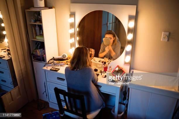"""mujer millenial haciendo maquillaje después de un tutorial. - """"martine doucet"""" or martinedoucet fotografías e imágenes de stock"""