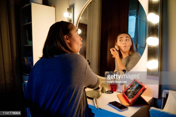 Millenial woman doing make-up following a tutorial.
