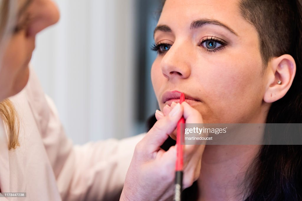Millenial woman having makeup done by mother. : Stock Photo