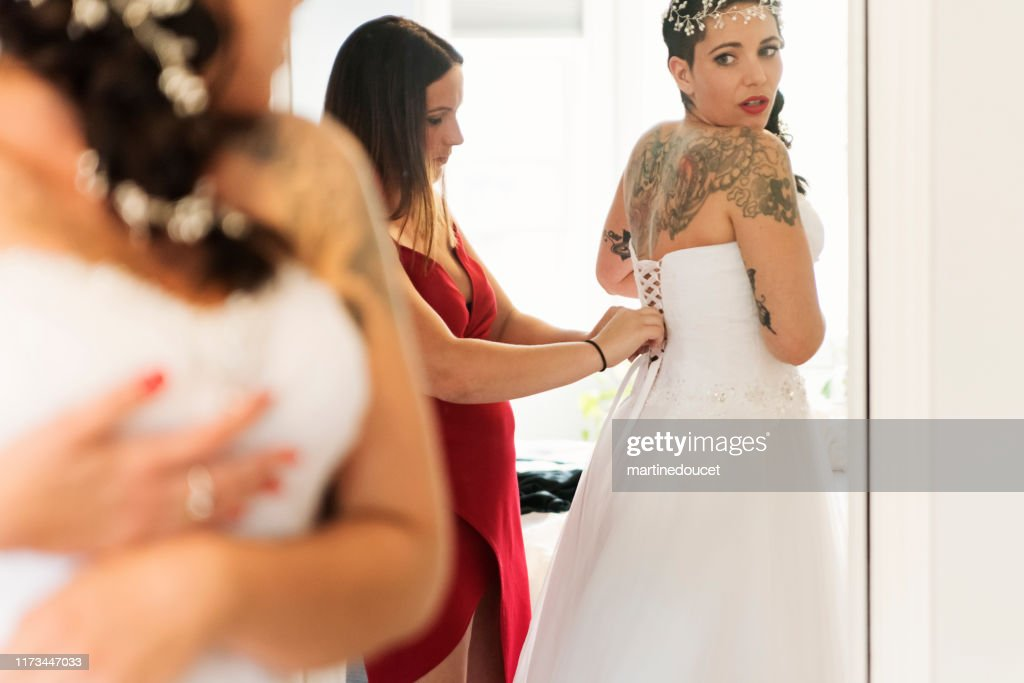 Millenial woman putting on her wedding dress. : Stock Photo