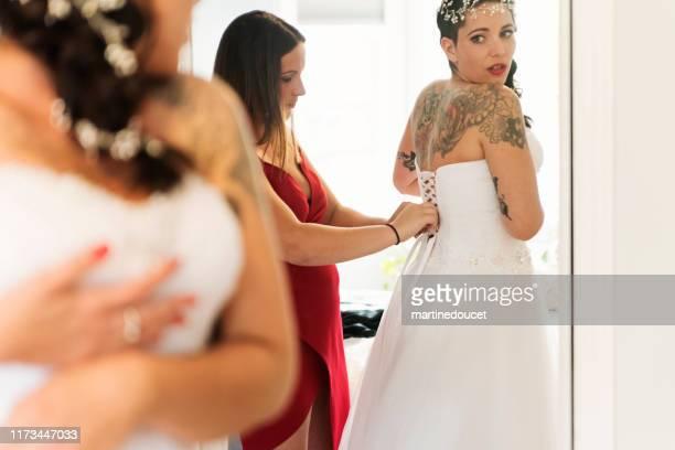 """mujer millenial poniéndose su vestido de novia. - """"martine doucet"""" or martinedoucet fotografías e imágenes de stock"""