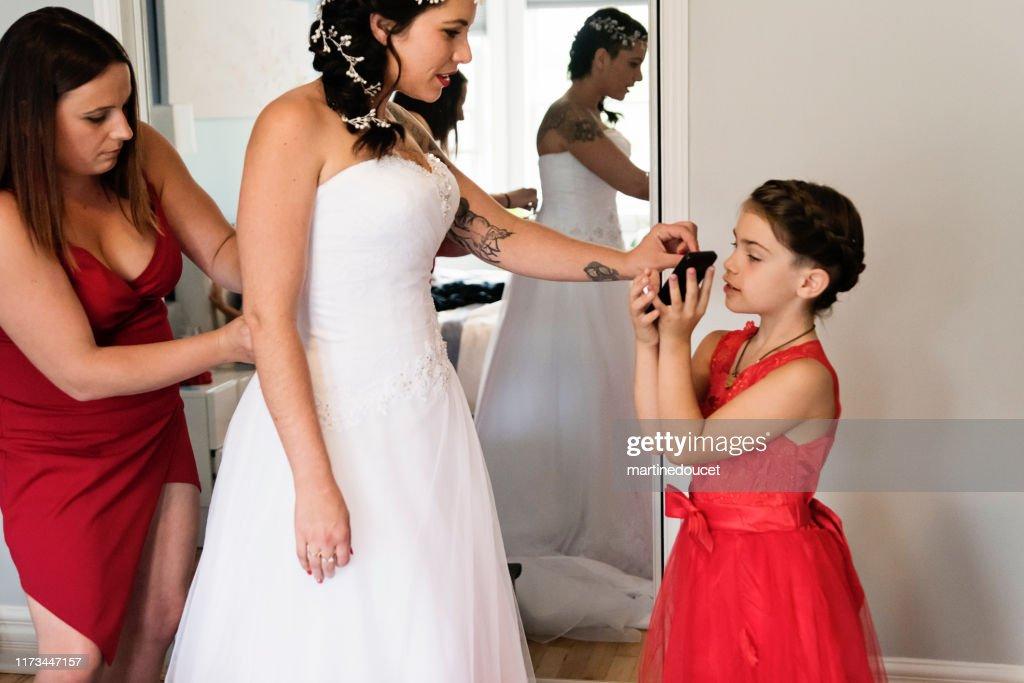 Millenial woman putting on her wedding dress. : Stock Photo