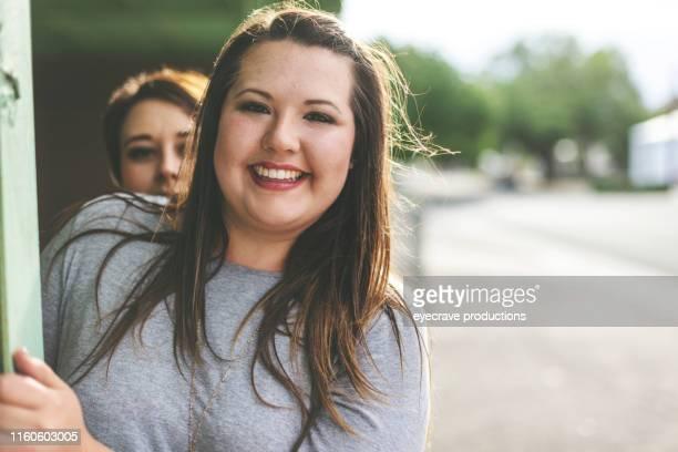millennial adult sisters genießen die gemeinsame zeit im urbanen umfeld - curvy woman stock-fotos und bilder