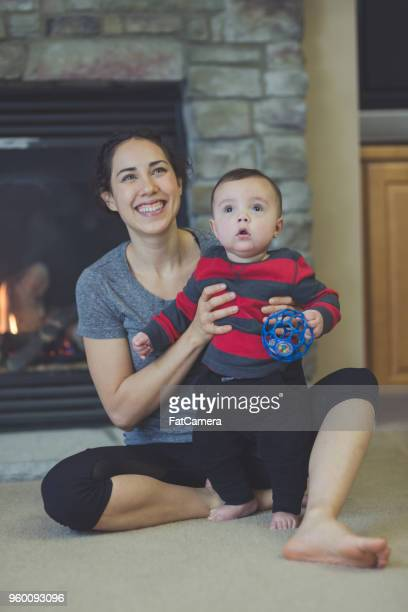 Millennial age ethnic mom plays on floor with her six-month old son