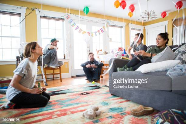 millennial at birthday party sitting and talking - room after party stock pictures, royalty-free photos & images
