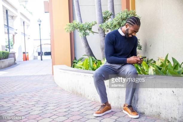 millennial black man depositing check mit smartphone - einzahlungsbeleg stock-fotos und bilder