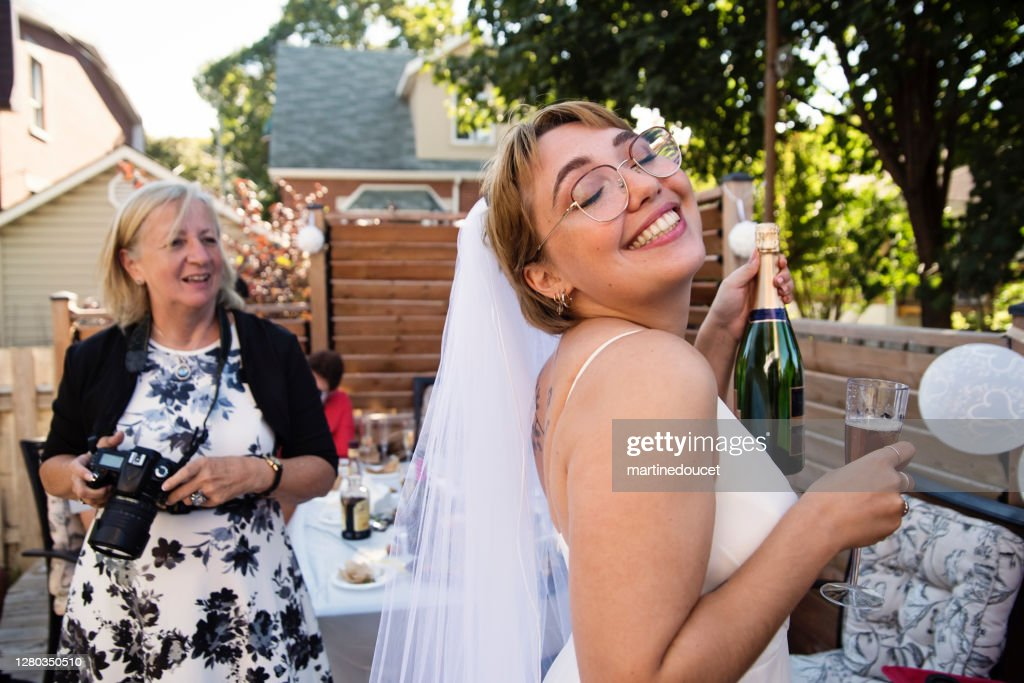 Millennial bride at wedding cocktail in backyard. : Stock Photo