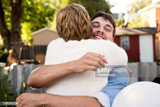 """millennial bride hugging brother at wedding cocktail in backyard. - """"martine doucet"""" or martinedoucet stock pictures, royalty-free photos & images"""