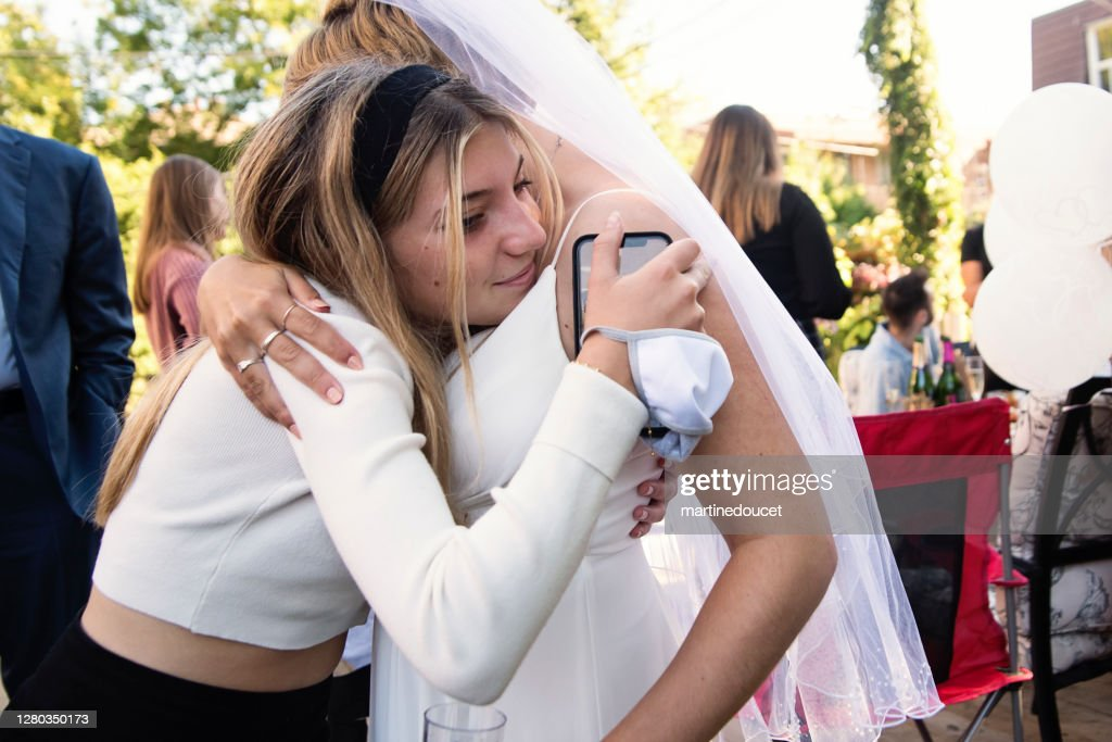 Millennial bride hugging cousin at wedding cocktail in backyard. : Stock Photo