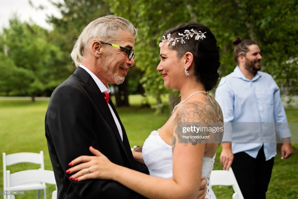 Millennial bride hugging father after wedding outdoors. : Stock Photo