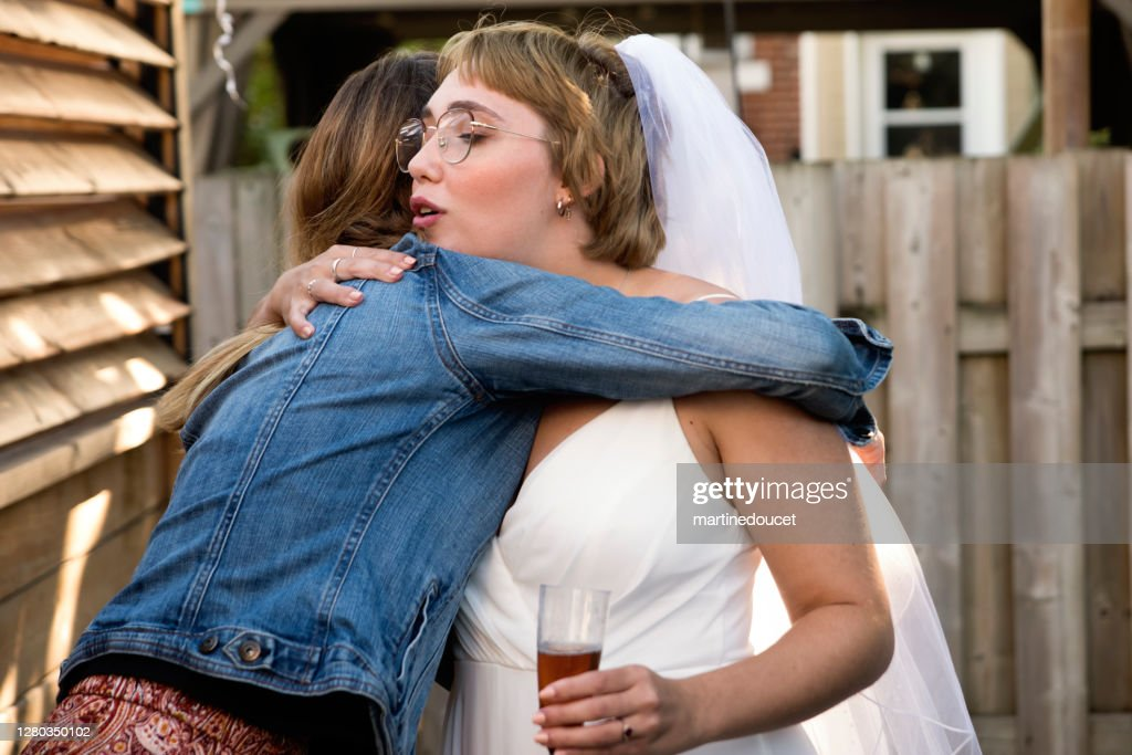 Millennial bride hugging godmother at wedding cocktail in backyard. : Stock Photo