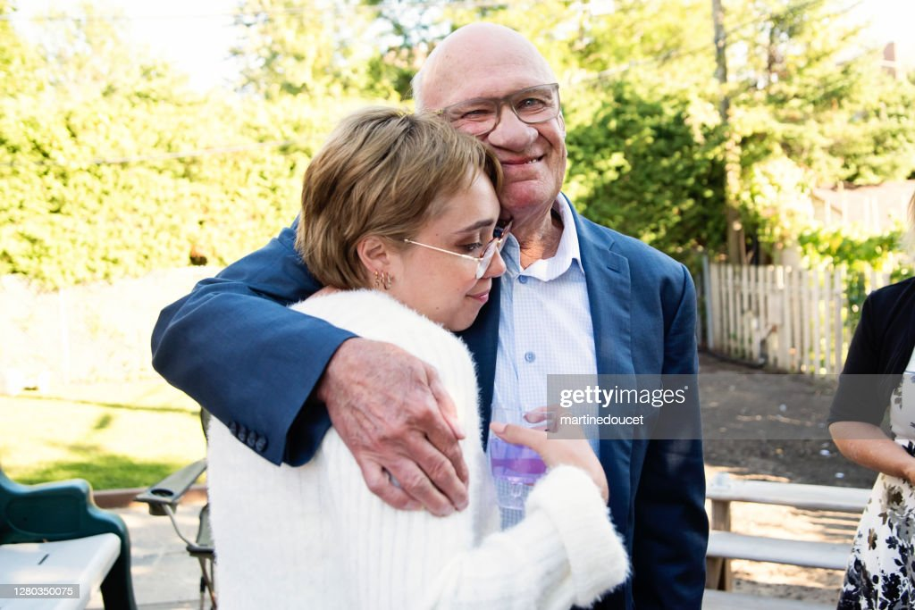 Millennial bride hugging grandfather at wedding cocktail in backyard. : Stock Photo
