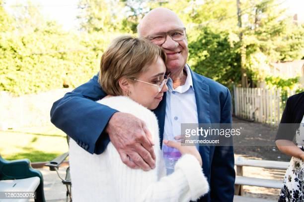 """millennial bride hugging grandfather at wedding cocktail in backyard. - """"martine doucet"""" or martinedoucet stock pictures, royalty-free photos & images"""