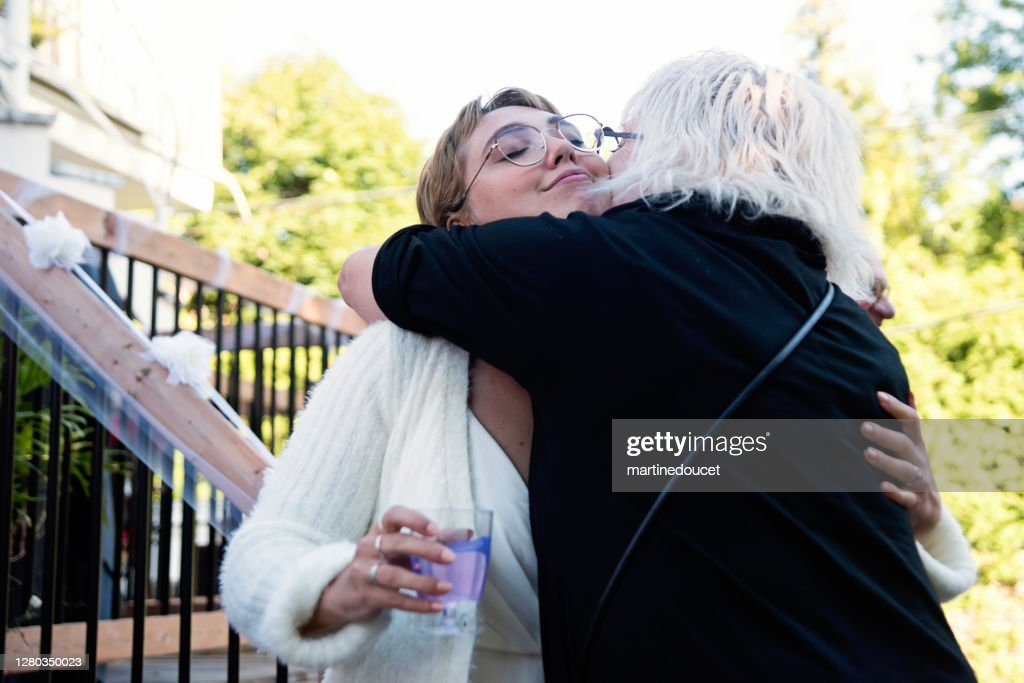 Millennial bride hugging grandmother at wedding cocktail in backyard. : Stock Photo