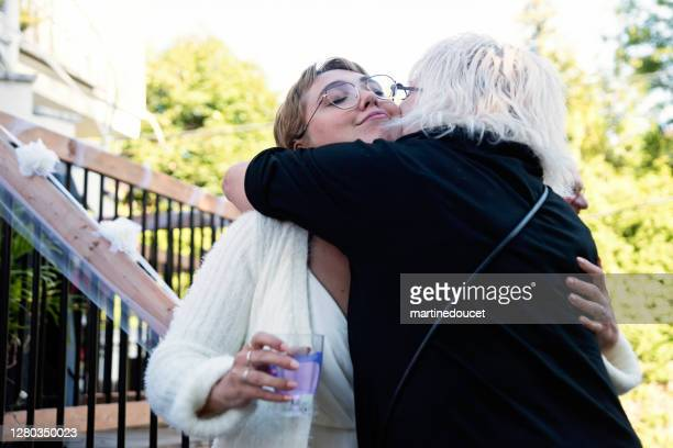 """millennial bride hugging grandmother at wedding cocktail in backyard. - """"martine doucet"""" or martinedoucet stock pictures, royalty-free photos & images"""
