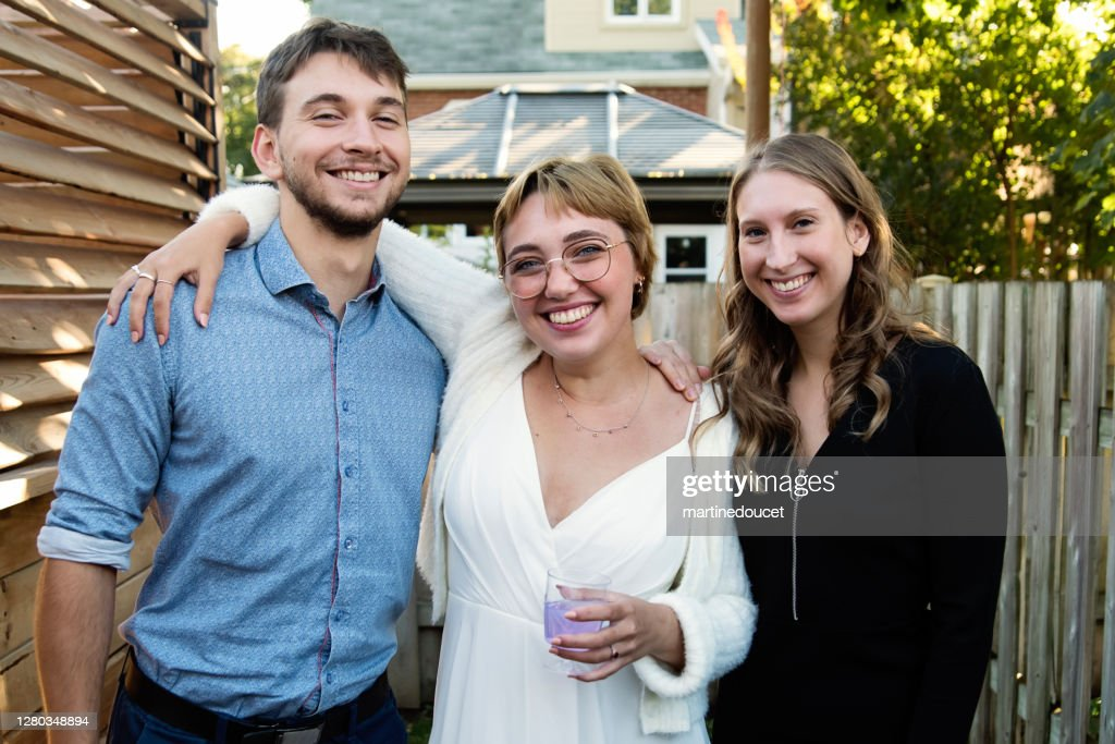 Millennial bride posing with brother and sister in backyard. : Stock Photo
