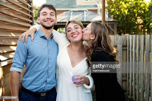 """millennial bride posing with brother and sister in backyard. - """"martine doucet"""" or martinedoucet stock pictures, royalty-free photos & images"""