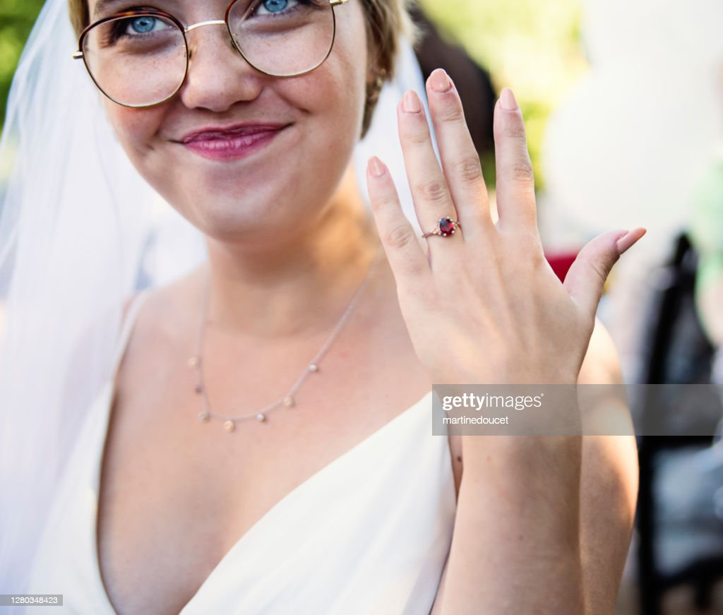 Millennial bride showing ring at wedding cocktail in backyard. : Stock Photo