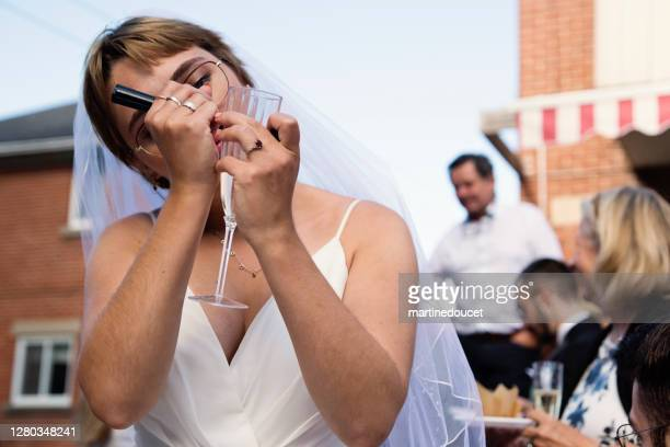 """millennial bride writing name on glass at wedding cocktail in backyard. - """"martine doucet"""" or martinedoucet stock pictures, royalty-free photos & images"""