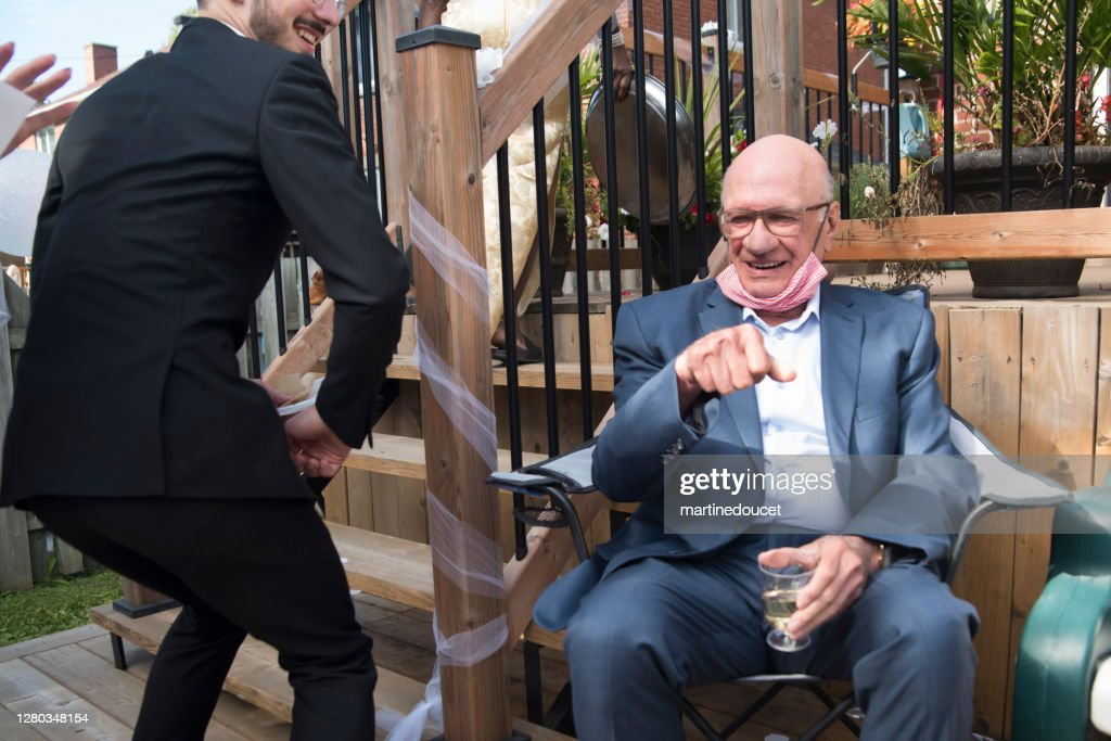 Millennial bridegroom doing elbow bump at wedding cocktail in backyard. : Stock Photo