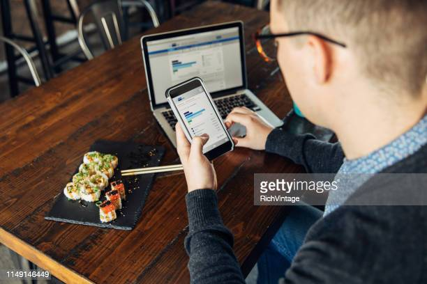 millennial checking finances on smart phone - bank account stock pictures, royalty-free photos & images