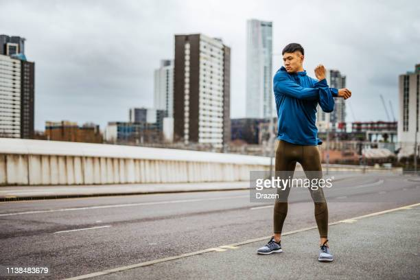 millennial chinese athlete exercising on cloudy and windy day - warming up stock pictures, royalty-free photos & images